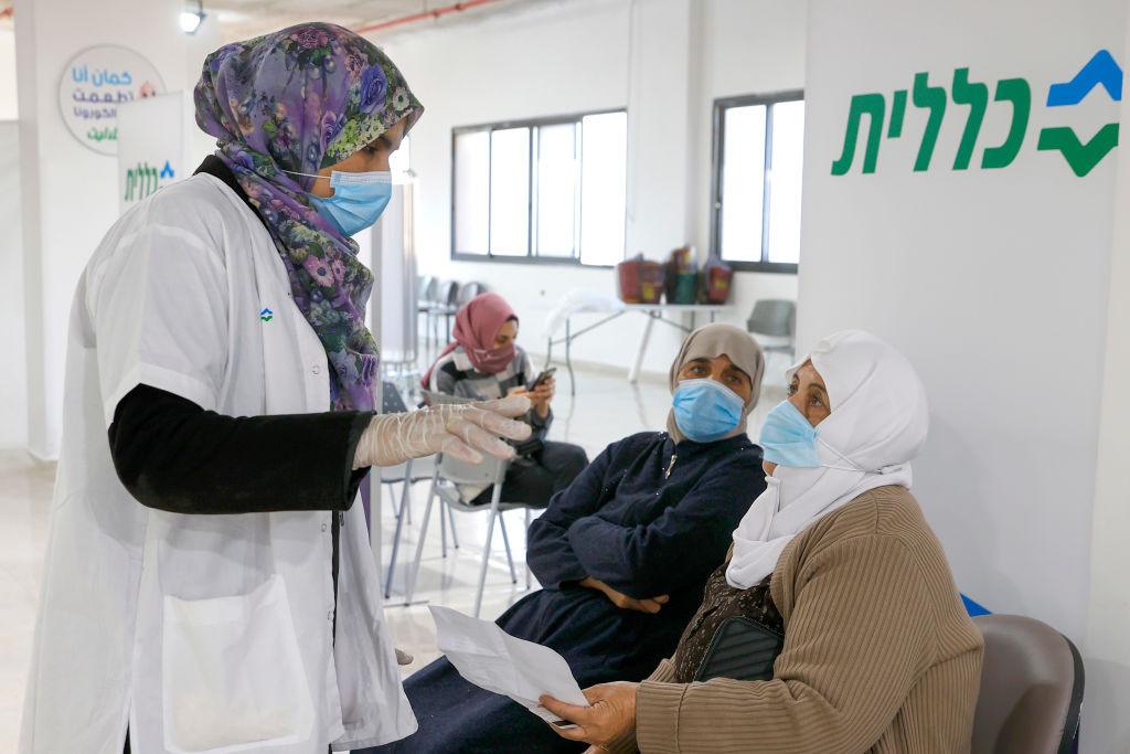 A healthcare worker speaks to an Arab Israeli woman before giving her a COVID-19 vaccine at Clalit Health Services, in the northern Arab Israeli city of Umm al Fahm , on January 4, 2021. - A healthcare worker (Photo by JACK GUEZ / AFP) (Photo by JACK GUEZ/AFP via Getty Images)